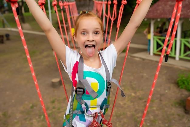 Niños - niña corre una carrera de obstáculos en un parque de cuerdas