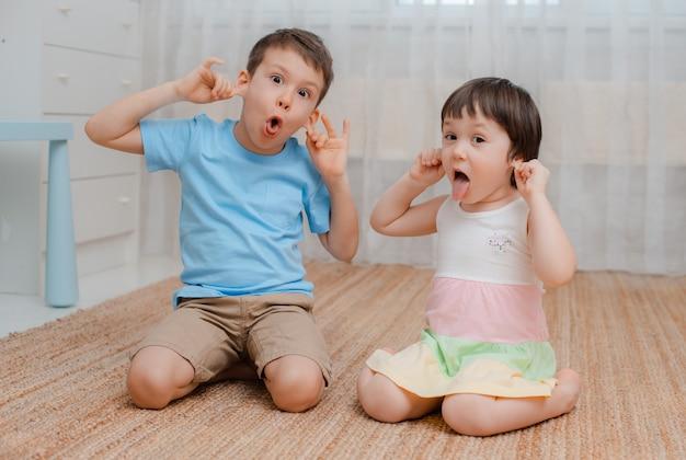 Niños, niña, habitación traviesa en el piso hacen una mueca de risa.