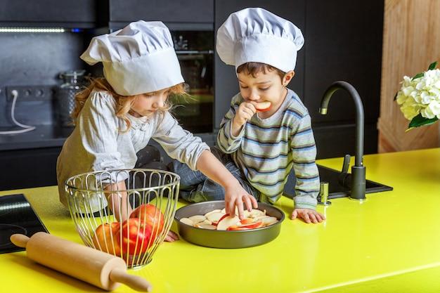 Los niños, niña y niño con gorro de cocinero preparándose para hornear pastel de manzana casero en la cocina