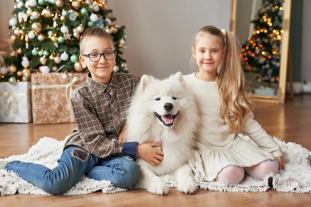 Niños niña y niño con perro samoyedo en escena navideña