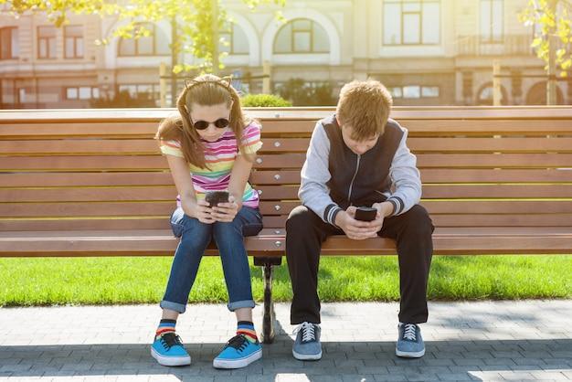 Los niños y niñas adolescentes juegan, leen, miran el teléfono inteligente.