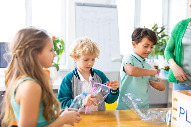 Niños y niñas. dos chicos guapos y una chica atractiva clasificando residuos en la escuela en la lección de ecología