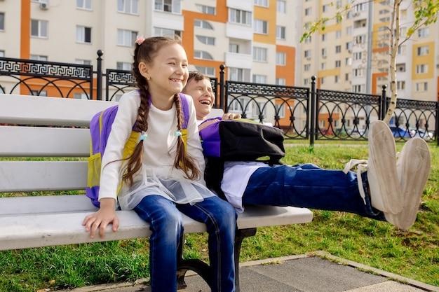 Los niños y niñas en edad escolar se sientan en un banco con mochilas brillantes y sonríen, miran a la cámara