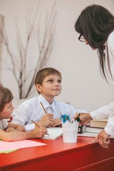 Los niños y niñas con el maestro en la escuela tiene un feliz