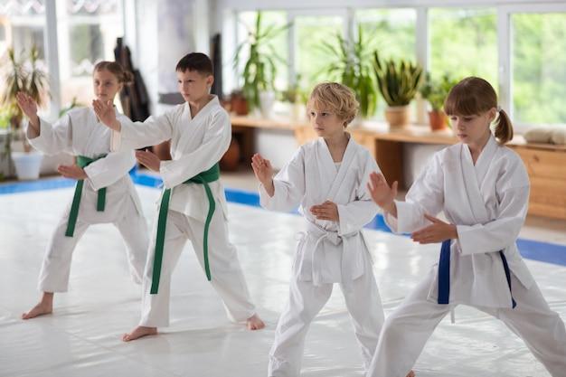 Niños y niñas repitiendo después de entrenador estudiando movimientos de aikido