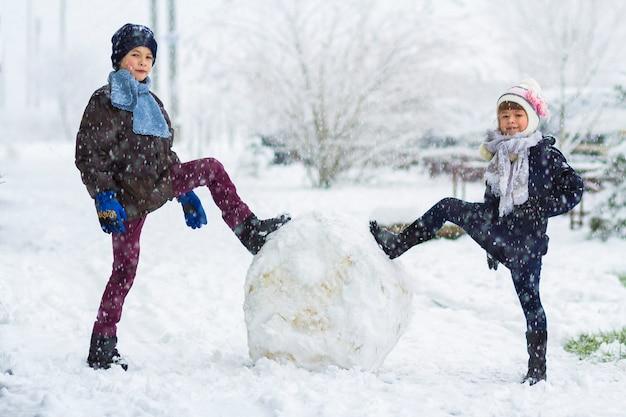Niños niño y niña al aire libre en invierno cubierto de nieve están haciendo un gran muñeco de nieve