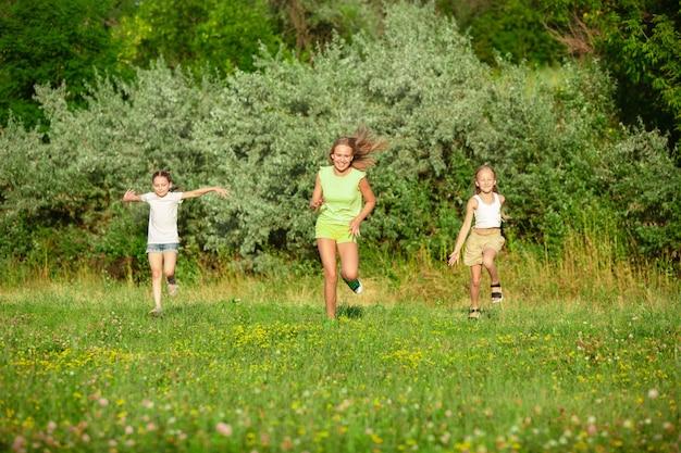 Niños, niños corriendo en la pradera en la luz del sol del verano