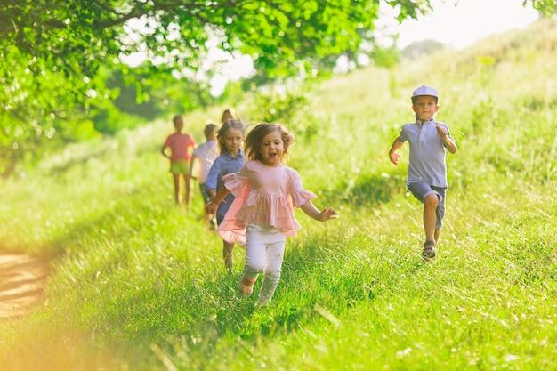 Niños, niños corriendo en la pradera, verano.