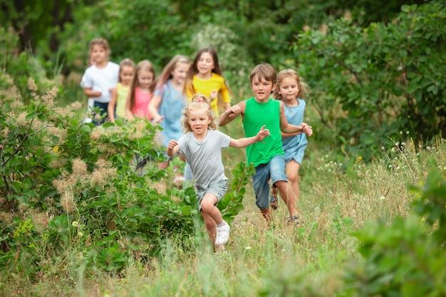 Niños, niños corriendo en prado verde