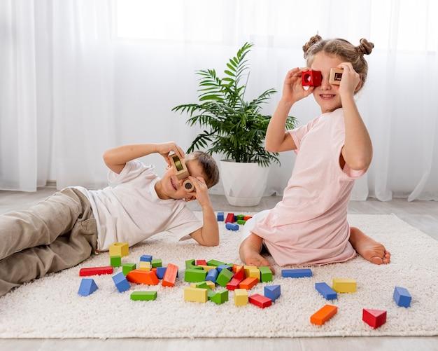 Niños no binarios jugando con juego colorido.
