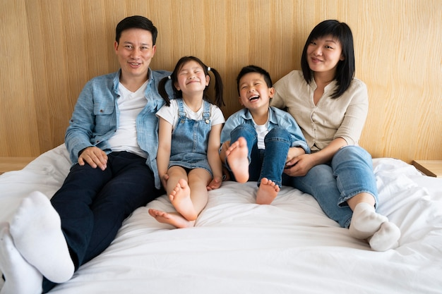 Niños y padres felices de tiro completo en la cama
