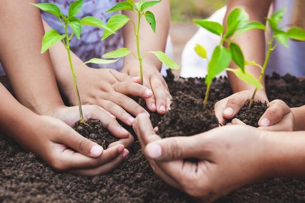 Niños y padres sosteniendo un árbol joven en las manos para plantar juntos en suelo negro