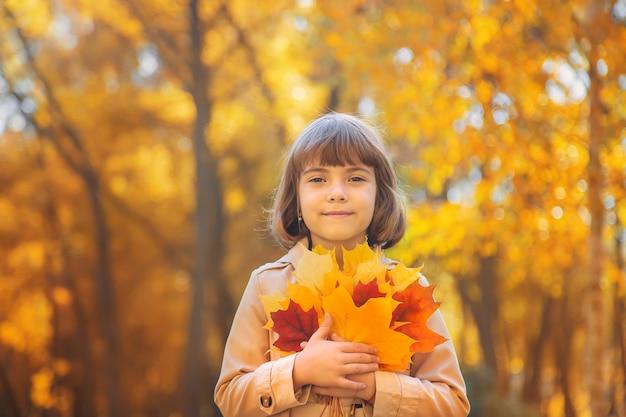 Niños en el parque con hojas de otoño. enfoque selectivo.
