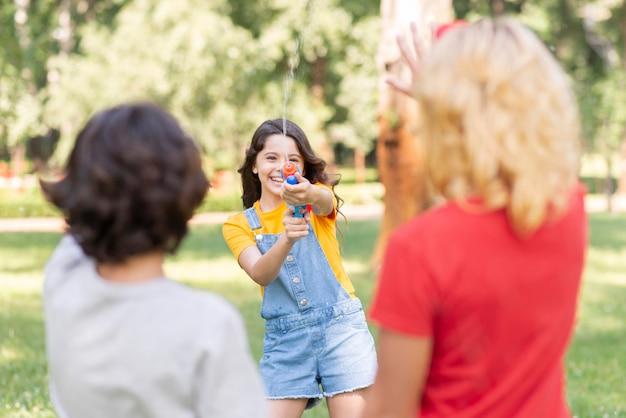 Niños en el parque jugando con pistola de agua