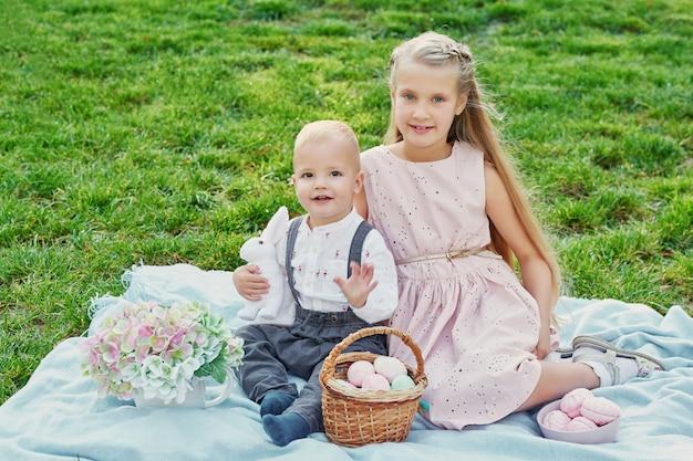 Niños en el parque de pascua picnic con huevos y conejo
