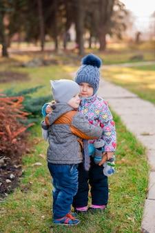Niños pequeños abrazados en el parque