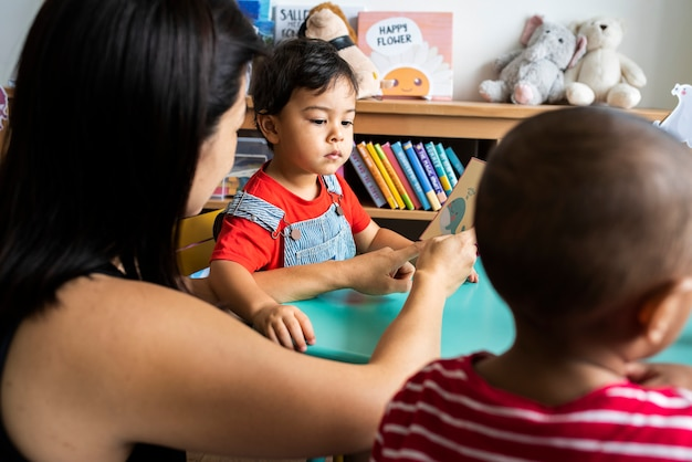 Niños pequeños aprendiendo el alfabeto inglés con sus padres.