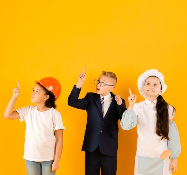 Niños pequeños apuntando hacia arriba vista frontal
