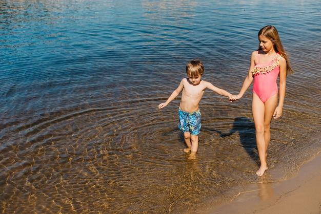 Niños pequeños caminando por la playa