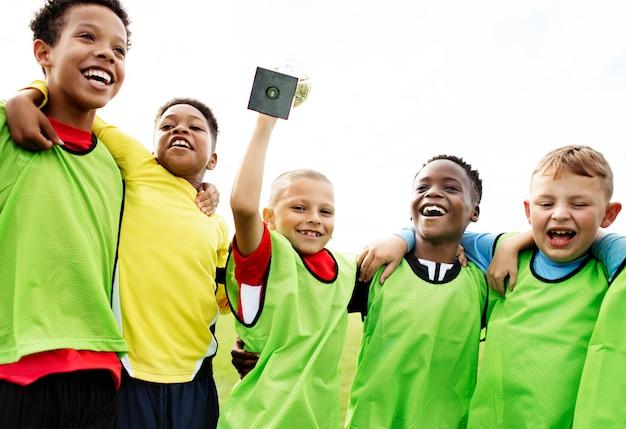 Niños pequeños en el campo celebrando su victoria.