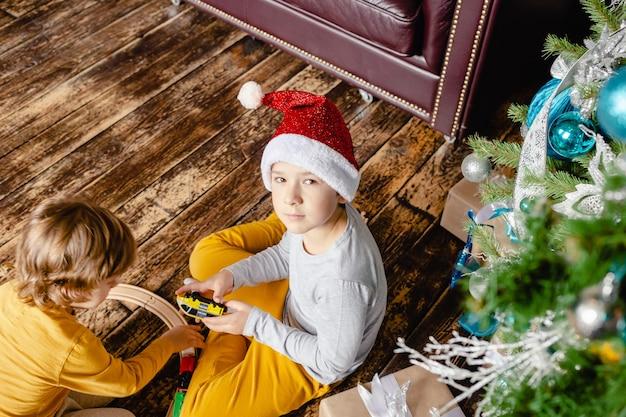 Niños pequeños construyendo vías férreas y jugando con un tren de juguete bajo el árbol de navidad.