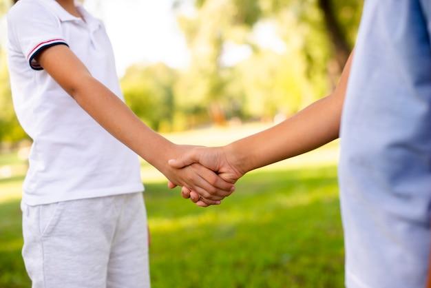 Niños pequeños dándose la mano en el parque