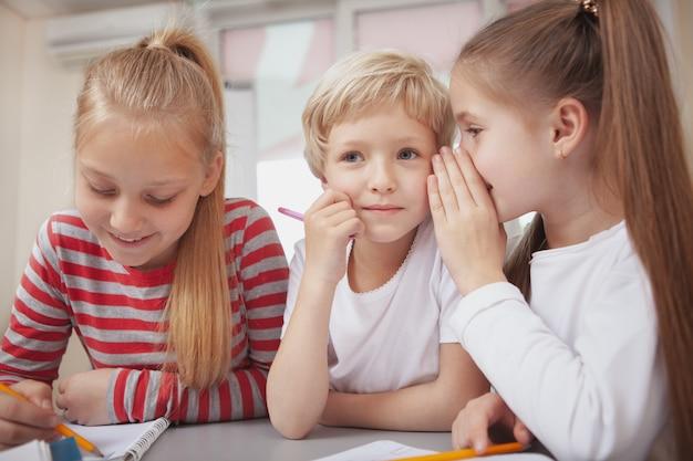 Niños pequeños dibujando en la clase de arte de la escuela primaria