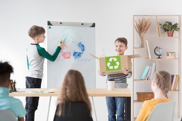 Niños pequeños dibujando signo de reciclaje
