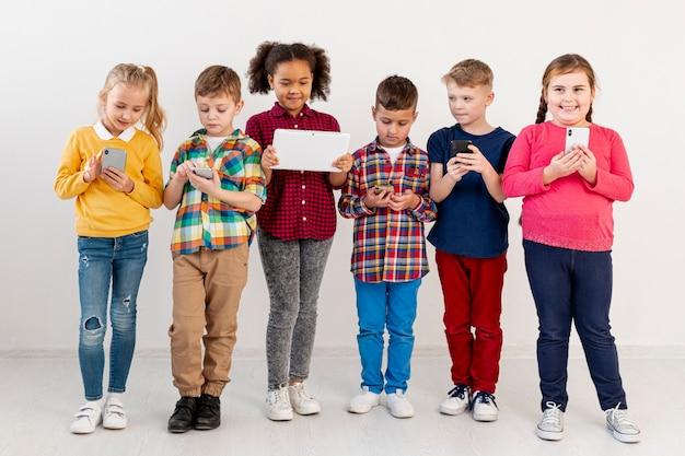 Niños pequeños con diferentes dispositivos.