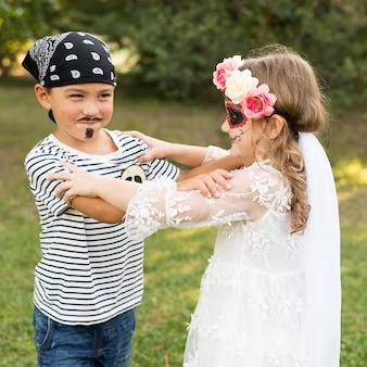 Niños pequeños con disfraces al aire libre.
