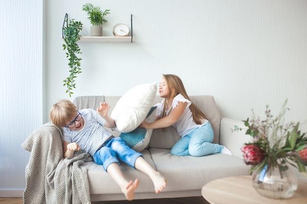 Niños pequeños divirtiéndose en el interior. niños jugando en el sofá. pelea de almohadas. hermano y hermana en casa haciendo desorden.