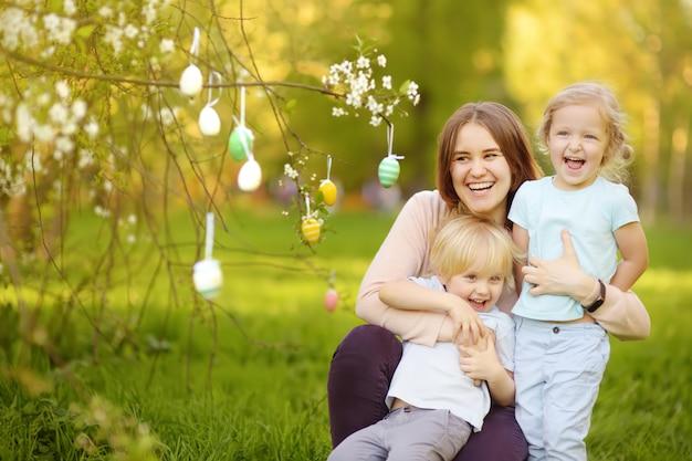 Niños pequeños encantadores con su madre cazando huevos pintados en el parque de la primavera el día de pascua