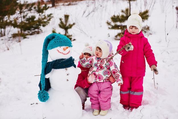 Los niños pequeños están mirando a un hermoso muñeco de nieve