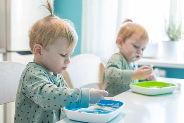 Los niños pequeños gemelos de chicos rubios en pijama hambrientos comiendo alimentos saludables en la cocina de casa.