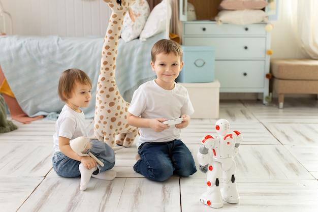 Los niños pequeños, hermano y hermana, se sientan en el suelo de la habitación, riendo y jugando con el robot.