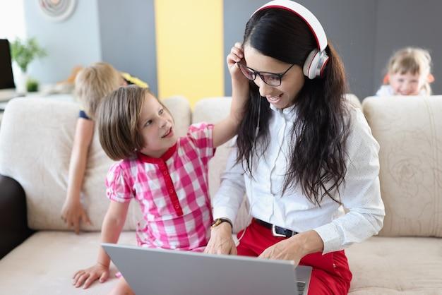 Los niños pequeños impiden que su madre trabaje con la computadora portátil en casa