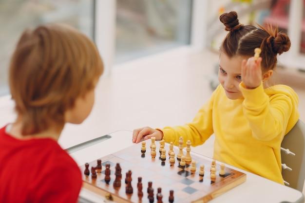 Niños pequeños jugando al ajedrez en el jardín de infantes o la escuela primaria