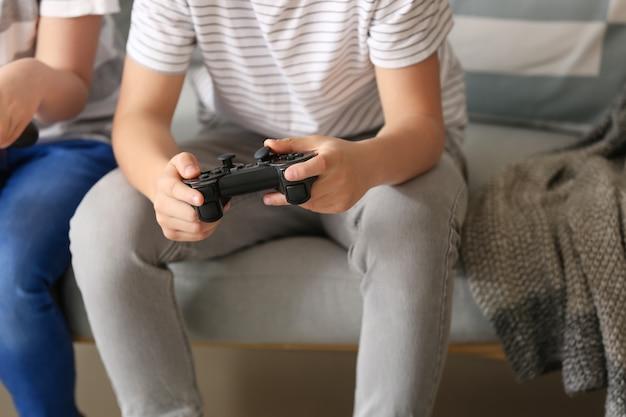 Niños pequeños jugando videojuegos en casa