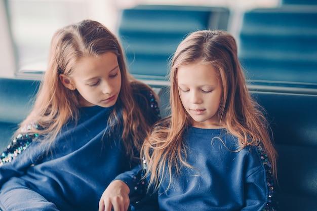 Niños pequeños juntos en el aeropuerto esperando el embarque