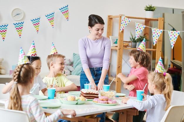 Uno de los niños pequeños lindos que cuenta una broma a sus amigos y una mujer joven feliz mientras está sentado junto a la mesa festiva en la fiesta de cumpleaños de casa