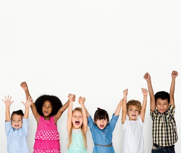 Niños pequeños manos arriba felices