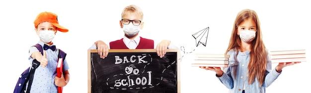 Niños pequeños con máscaras de protección contra el virus corona en la escuela.