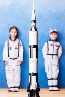 Niños pequeños, niña y niño jugando en astronauta en traje de astronauta blanco y soñando con volar al cosmos quedándose cerca del cohete de juguete