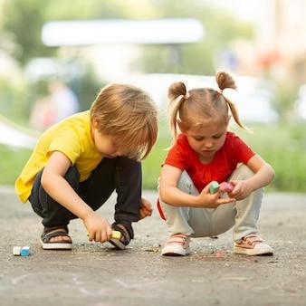 Niños pequeños en el parque dibujando con tiza