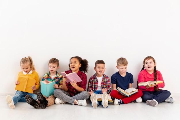 Niños pequeños en el piso leyendo