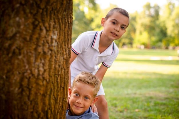 Niños pequeños posando detrás de un árbol