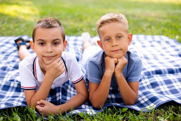 Niños pequeños posando en una manta de picnic