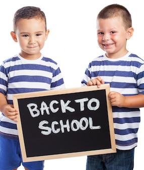 Niños pequeños sonriendo con una pizarra negra con el mensaje