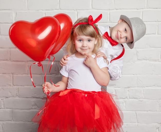 Niños pequeños sosteniendo y recogiendo globos de corazón. día de san valentín y el concepto de amor, sobre fondo blanco.