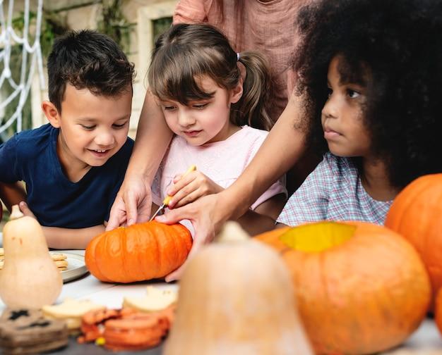 Niños pequeños tallando halloween jack-o-lanterns